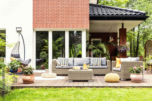 Real photo of a beautiful terrace with garden furniture, plants and swing - 210111033