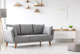 Simple, gray sofa standing next to a white cupboard in living room interior with decorations on wooden shelves. Real photo - 210111866