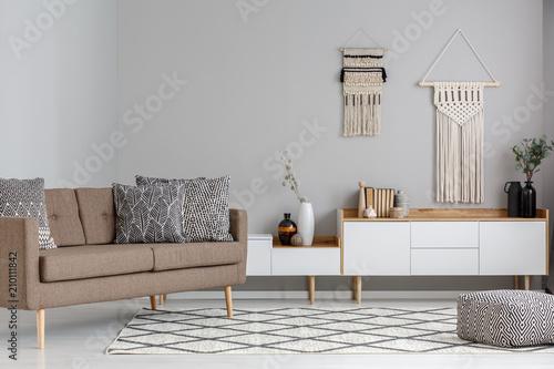 Prawdziwe zdjęcie poduszek z botanicznym wzorem na brązowej kanapie stojącej obok białych kredensów z makrama wiszącą w naturalnym wnętrzu salonu