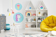 Yellow pouf in colorful child's room interior with lamps and posters