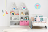 Colorful lamps above rug in modern scandi kid's bedroom interior with poster above bed