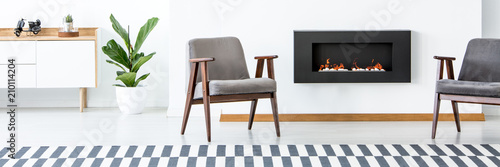 Foto Murales Two grey armchairs standing in white living room interior with fireplace, fresh green plant and cupboard with motorcycle model and cactus