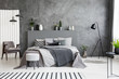 Grey armchair and stool near bed with headboard in bedroom interior with black lamp. Real photo