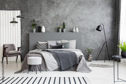 Leinwandbild Motiv Grey armchair and stool near bed with headboard in bedroom interior with black lamp. Real photo