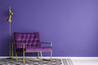 Ultra violet armchair with golden details and lamp standing on the empty wall