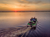 Tourists visiting Danube Delta in a motor boat, taking pictures at sunset in the Danube Delta, Romania
