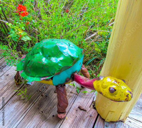 Foto Murales Colorful Sculpture of Turtle on wooden floor near green grass.  Recycled Scrap Metal Yard Art. Beautiful garden decor object. Summer view outdoors.