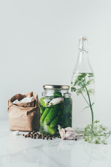 glass jar with preserved cucumbers, glass bottle with dill and salt on table