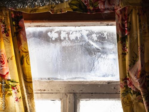 shabby frozen window in old russian rural house - 210138441