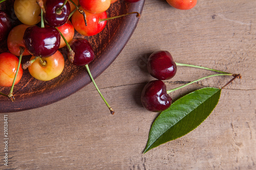 Fotobehang Kersen Clay plate with yellow and red sweet cherry on wooden background.