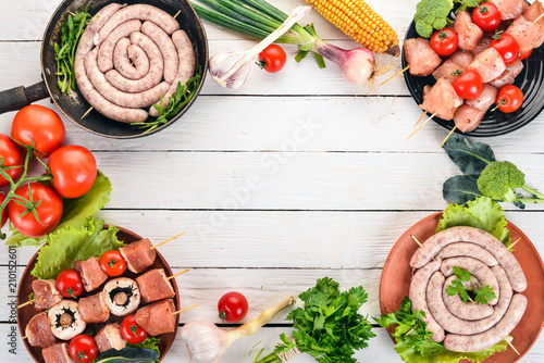 Assortment of meat for barbecue. Sausages, skewers and vegetables. On a wooden background. Top view. Copy space. - 210152601