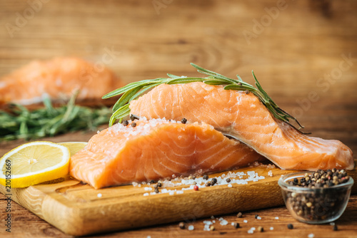 Raw salmon fish fillet on wooden background.
