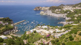 Aerial view of the beach and the small harbor of Cala Feola on the island of Ponza, in Italy. There are many boats and motorboats of tourists anchored in the bay and sheltered in the mountains. - 210155652