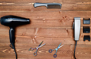 Hairdresser tools on wooden background. Top view on wooden table with scissors, comb, hairclipper and hairdryer, free space. Barbershop