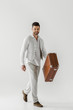 smiling stylish male traveler in linen clothes carrying vintage suitcase isolated on grey background