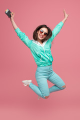 Stylish girl jumping up on pink