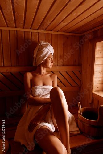 dziewczyna w zabiegach spa w tradycyjnej saunie z pędzlem do skóry i myjki. relaksuje się owinięty w biały ręcznik