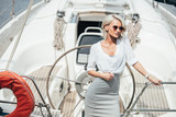 beautiful young blonde woman in sunglasses standing on yacht - 210170483