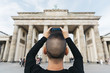 Leinwanddruck Bild - young man taking a picture of the Brandenburg Gate