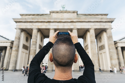 Leinwanddruck Bild young man taking a picture of the Brandenburg Gate