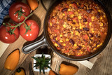 Chili con carne in a clay pan. - 210174079