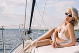 attractive young woman in sunglasses and bikini looking at camera on yacht - 210177827