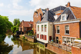 canal with old buildings in Appingedam, Netherlands - 210185635