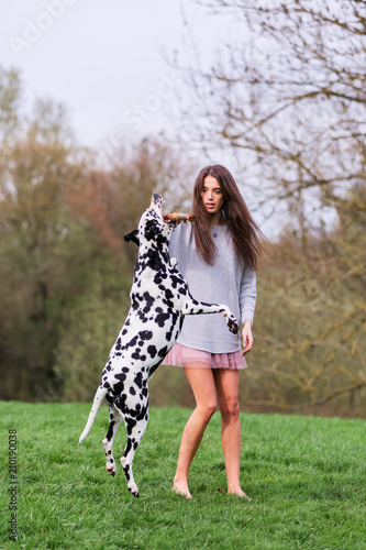 young woman plays with Dalmatian dog outdoors