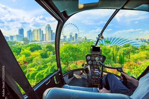 Helicopter cockpit interior flying on Aerial view of Singapore cityscape and garden park by the bay. Famous marina bay promenade of Singapore.