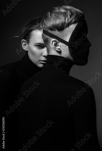 Portrait of woman with man in face mask posing on dark background © FlexDreams