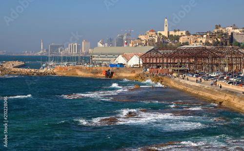 Zatoka Morza Śródziemnego w Tel Awiwie-Jaffie, promenada nadmorska w starej Jaffie, budynki, zaparkowane samochody, skały w wodzie, w tle, nieco rozmyte, drapacze chmur nowoczesnej częsci miasta