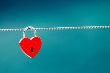 Red love lock padlock on bridge outdoor