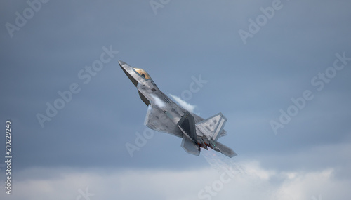 obraz PCV F-22 Raptor in a high G maneuver, with condensation trails forming above the wing and the hot jet stream visible against the clouds