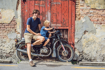 Dad and son on an old motorcycle. Penang
