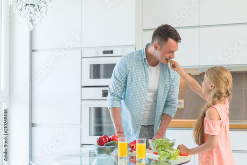 Wall mural Dad and daughter cooking at home