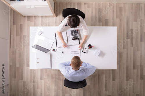 Two Businesspeople Analyzing Bill - 210272454