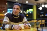 Man drinking coffee in coffee shop - 210274256