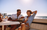 Smiling couple sitting on a boat with drinks