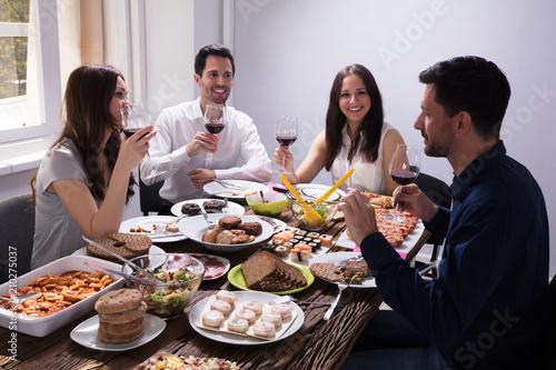 Fototapeta Friends Enjoying Food With Glass Of Wine