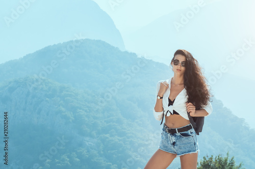 Fotobehang Lichtblauw Attractive young girl with backpack enjoying sunset on peak of mountain. Tourist traveler on blue background valley landscape view mockup for text. Attractive slim brunette mixed race Asian Caucasian