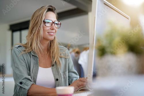 Leinwanddruck Bild Beautiful woman working on desktop computer, co-working area