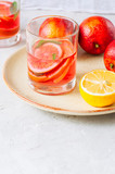 Refreshing blood orange and lemon water or infused water in a glass on a white stone background