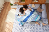 High angle view of pretty Asian woman sleeping peacefully in cozy bed with smartphone in hand, interior of modern bedroom on background - 210312257