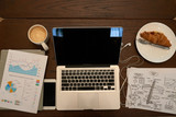 High angle view of wooden cafe table: laptop, smartphone, documents, cup of fragrant coffee and appetizing croissant waiting for its owner - 210314630