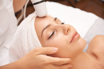 Relaxed woman enjoying facial beauty procedure carried out with special electric device © DragonImages