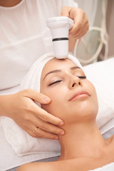 Modern beautician carrying out spa skincare procedure with special electric device © DragonImages