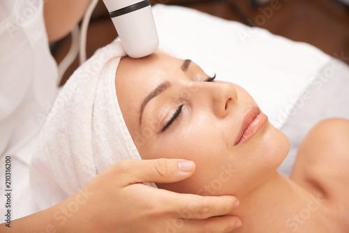 Zrelaksowana kobieta korzystających zabieg kosmetyczny twarzy przeprowadzane ze specjalnym urządzeniem elektrycznym