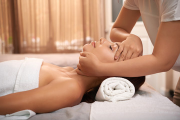 Young woman having calming massage on her face while relaxing in luxurious spa salon © DragonImages