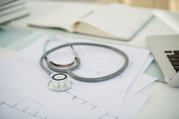 Close-up of stethoscope and cardiogram on the desk at doctor's office © DragonImages