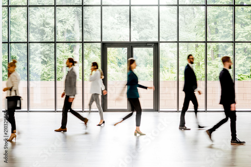 Business people walking at the modern hall on the window background indoors. long exposure image technic with motion blurred people - 210325865